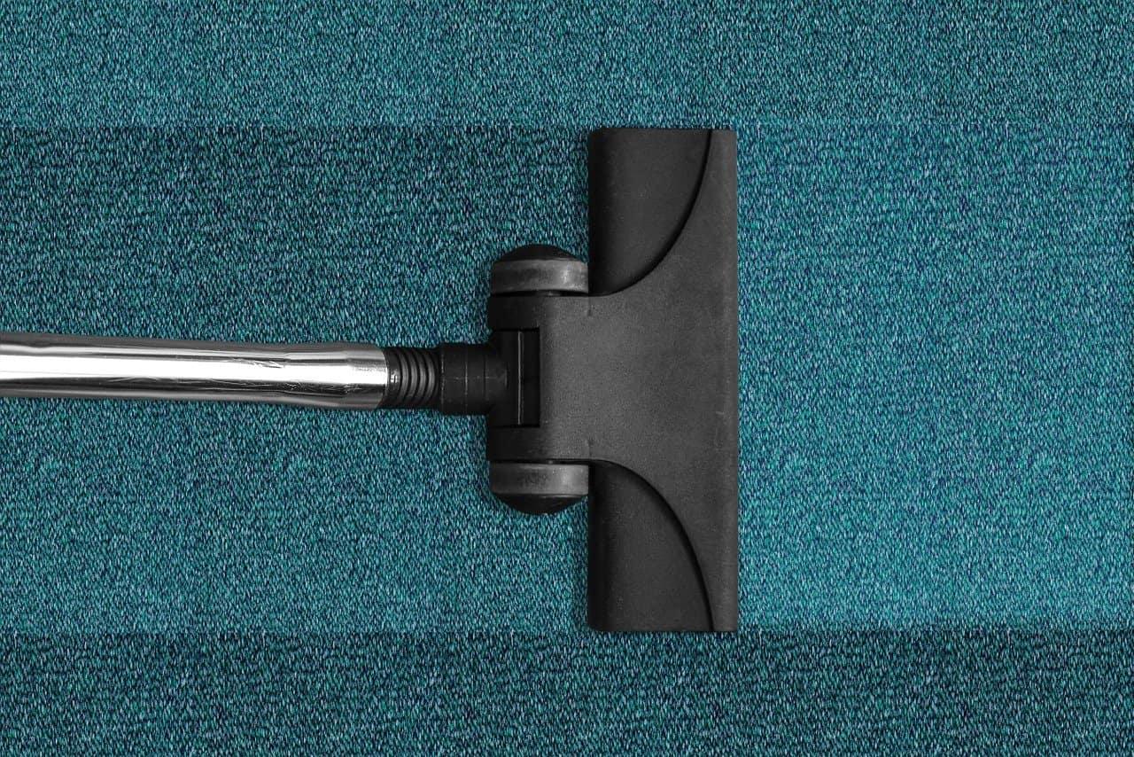 שואב אבק על גבי שטיח בצבע טורקיז